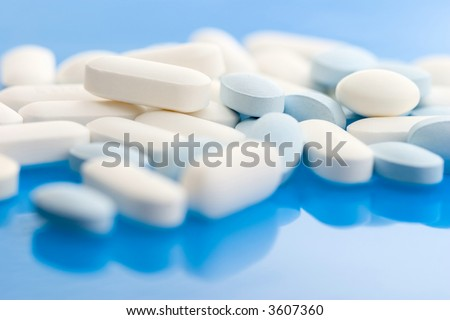 Pills on blue background; Shallow depth of field.