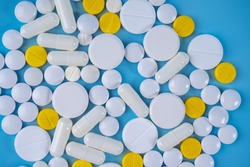 Pills on the table. Pharmacology. Treat disease. Medical background. White and yellow pills on a white background.