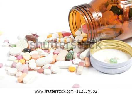 Pills pouring out of the brown bottle. - stock photo