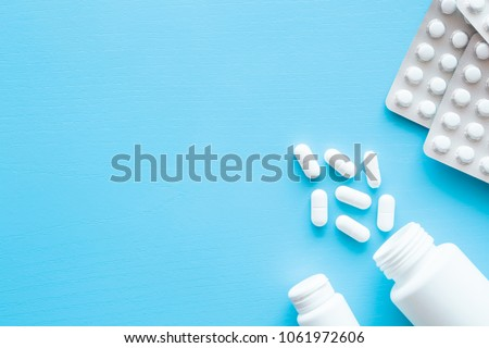 Pills spilled out of white bottle on blue background. Mock up for special offers as advertising or other ideas. Medical, pharmacy and healthcare concept. Copy space. Empty place for text or logo.