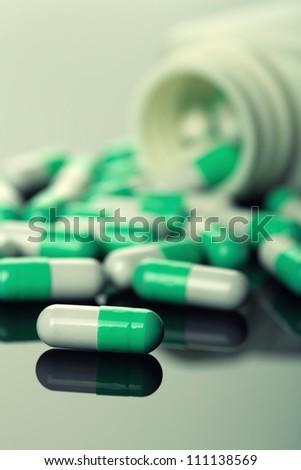 Pills spilling from an open bottle. Toned