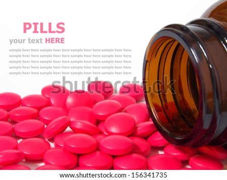 Pills spilling out of a pill bottle isolated on white