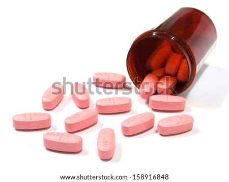 Pills spilling out of a pill bottle isolated on white background