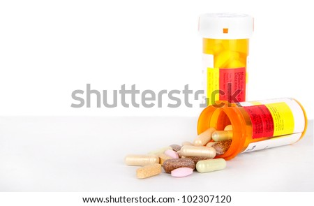 Pills spilling out of a prescription bottle, isolated background