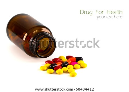 Pills, Tablets and Capsules spilled from a bottle on white background with copy-space.