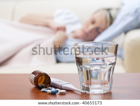 Pills, thermometer and water with girl in bed in background