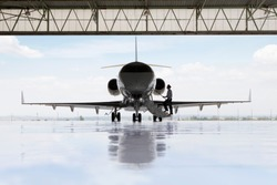 Pilot boarding private jet in hangar