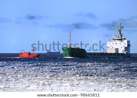 Pilot boat and a Cargo ship entering of Riga in winter