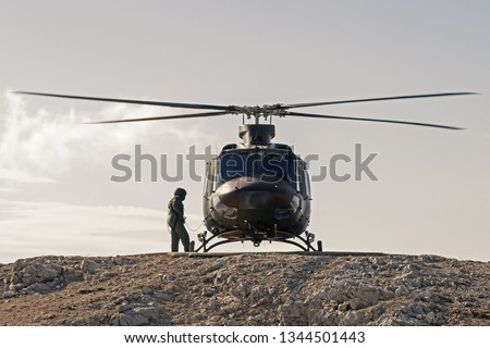 Pilot checking military helicopter before taking off from helipad on top of mountain. Military, airforce, defense and mountain rescue concepts. Zdjęcia stock ©