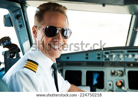 Pilot in cockpit. Rear view of confident male pilot looking over shoulder and smiling while sitting in cockpit