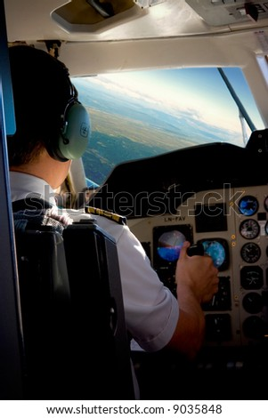Pilot in the cockpit of a small commercial aircraft above a rural landscape.
