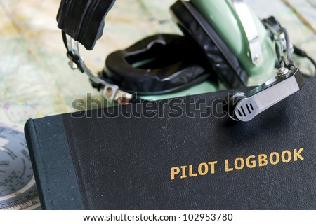 pilot logbook and headset on a map