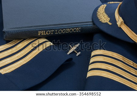 Pilot logbook with Captain 4 gold stripes on sleeves with Captain hat and Dash 7 pin. Сток-фото ©
