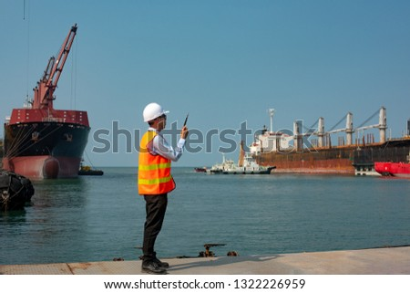 pilot or harbor master, port control or supervisor in command to takes the commcercial ship berthing alongside terminal for operation in wharf, tugs boat assist for safety circumstance in terminal #1322226959
