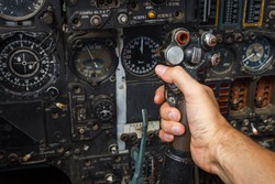 Pilot's hand on the military aircraft control knob. In the cockpit of an old, Soviet military jet. Close-up. Text translation from Russian