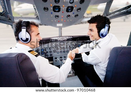 Pilots in an airplane cabin handshaking after a successful flight