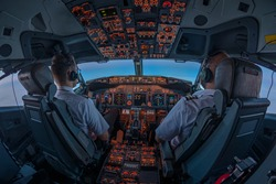 Pilots in the cockpit of jet commercial airplane during the flight with first rays of the warm sunrise entering through the flight deck window