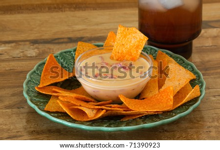 Pimento, peppers and cheese dip served with tortilla chips and mixed drink on bar as Happy Hour Snacks.