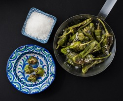 Pimientos de padron. Grilled green peppers with salt on the side. Spanish cuisine. Flat lay. Roasted