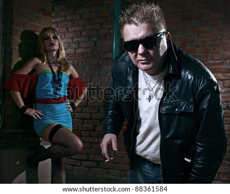 pimp and a prostitute in back alley - stock photo