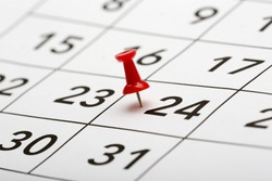 Pin on the date number 24. The twentyfourth day of the month is marked with a red thumbtack. Focus point on the red pin.