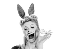 Pin-up Bunny. Beautiful blonde girl with bunny ears and Easter egg. Easter Cards. Pin up Easter. Bunny ears concept. Bunny woman. Hand with color Easter eggs. Isolated white background