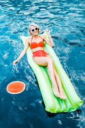 pin up girl in swimsuit relaxing on green inflatable mattress in swimming pool with watermelon