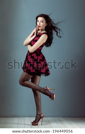 Pin up girl sex with flying hair in a dress smiling and surprised gasps of amazement
