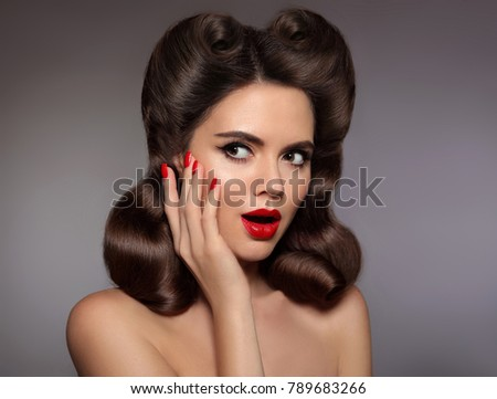 Stock Photo Pin up girl surprised with red lips makeup and manicured nails, glossy wavy hairstyle. Retro woman looking to the side. Expressive facial expressions. Presenting your product.