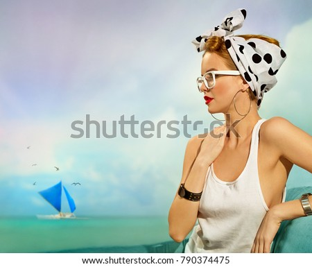 Pin-up girl with a headscarf in white t-shirt sitting by the sea