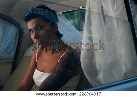 Stock Photo pin-up lady with tattoos in retro car