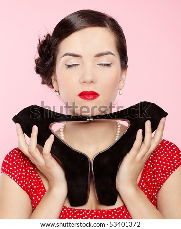 pin-up style portrait of beautiful brunette girl posing with court shoes