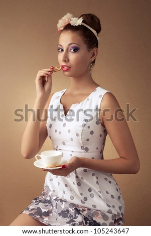 pin-up style portrait of beautiful brunette girl with tea cup