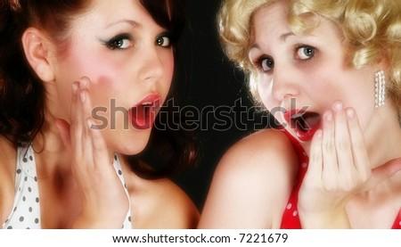Pin-up style retro portrait of two beautiful flirty young women.