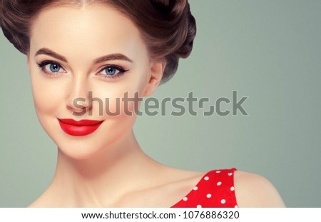 Pin up woman portrait. Beautiful retro female in polka dot dress with red lips and manicure nails and old fshion hairstyle hand pointing to side. Studio shot.
