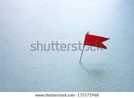 pin with a red flag on blue textured surface