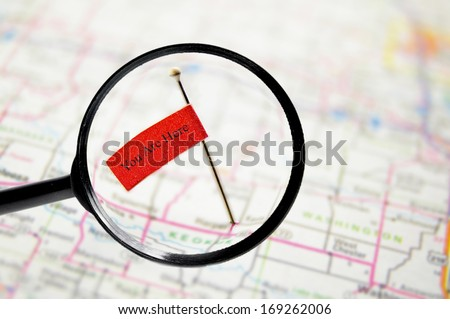 pin with You Are Here text, stuck into a map with magnifying glass