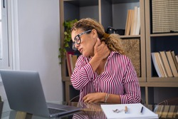 Pinched nerves, tensed sore muscles, fibromyalgia ache due sedentary lifestyle and incorrect posture concept. Caucasian ethnicity frowning woman sitting at desk in front of laptop, touch neck pain