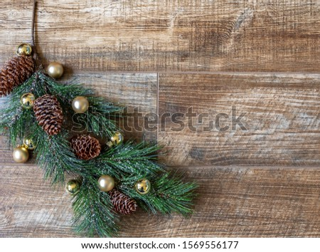 Pine bough with pine cones & gold ornaments on rustic wood background, for Christmas. Great for adverts, flyers,greeting cards, web design, etc. Can be used vertical or horizontal,flip left/right.