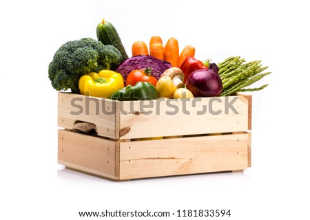 Pine box full of colorful fresh vegetables on a white background, ideal for a balanced diet, contains broccoli, cucumber, onion, asparagus, peppers, carrots, and potatoes #1181833594
