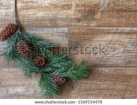 Pine branch with pine cones  on rustic wood background, for Christmas. Great for adverts, flyers,greeting cards, web design, etc. Can be used vertical or horizontal,flip left/right.