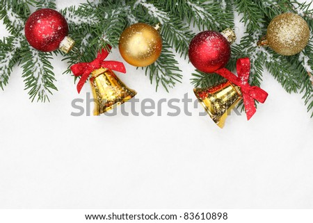 Pine branches, shiny balls and bells on snow with copy space.