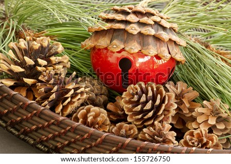 Pine Cone Bell An unusual red pine cone bell.  The bell is surrounded by fresh pine needles and pine cones.