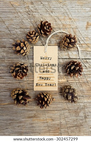Pine cones and tag. Space for text. Pine cones on wooden background
