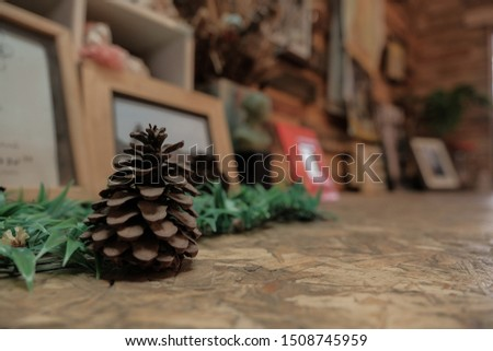 Pine cones on a wooden table decorated with artificial grass and picture frames. Working corner. Reading corner. #1508745959