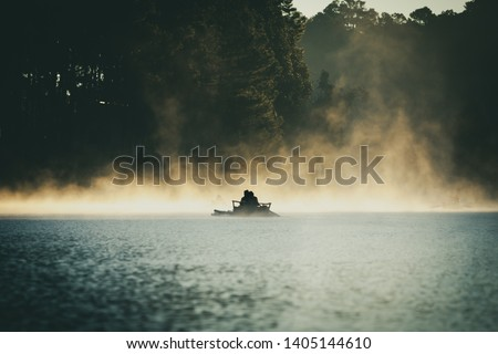Pine forest with foggy over the reservoir while tourists rafting through the fog in the morning at Pang-ung, Mae Hong Son Province, North of Thailand.