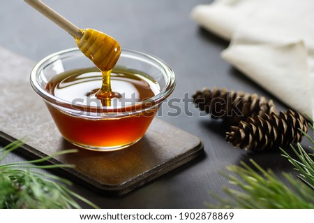 Pine honey in jar or bowl with honey stick and pine cones on rustic table, healthy food