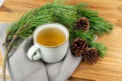 Pine needles tea in old cup. Healthy winter beverage in camping, pine tree needles tea in vintage mug. Medicine scurvy, source of vitamin C and carotene