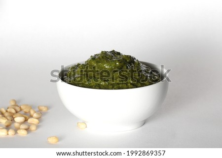 pine nuts and basil pesto sauce stands on a white background