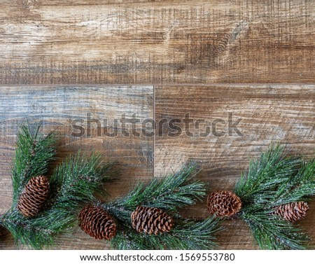 Pine swag with pine cones  on rustic wood background, for Christmas. Great for adverts, flyers,greeting cards, web design, etc. Can be used vertical or horizontal,flip left/right.